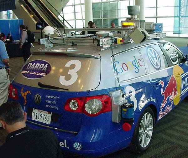 Photograph of Winning Stanford Vehicle for the DARPA challenge. It is a blue and silver hatchback vehicle covered in logos.