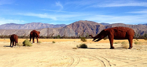 Redish-brown elephant sculptures in a desert with mountains in the distance.
