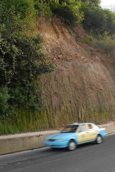 Eroding hill along a roadside with a cab speeding by.
