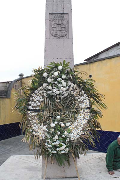 Photograph of memorial with large wreath.