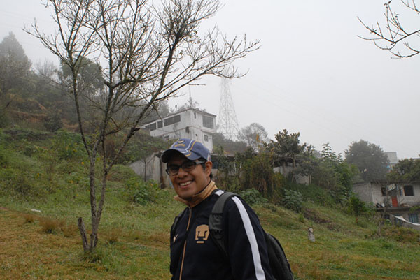 Photograph of a smiling man with houses on a hillside in the background.