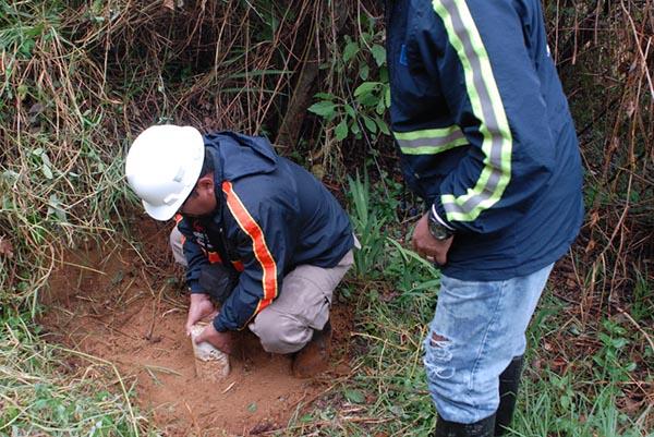 Two men taking samples in the soil.