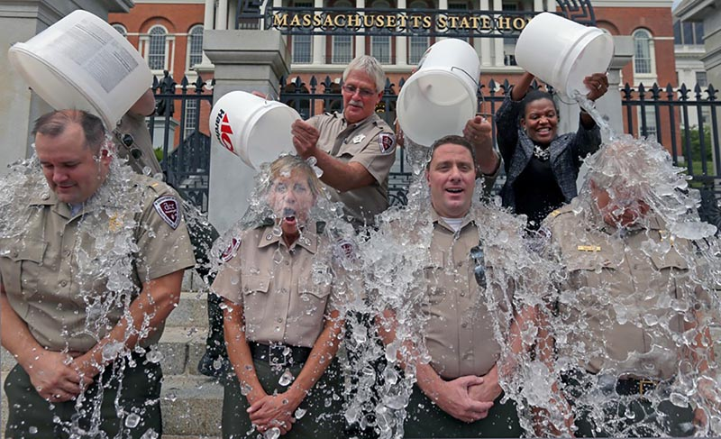Photograph of four uniformed individuals having buckets of ice water dumped on their heads in front of the Massachusetts State House