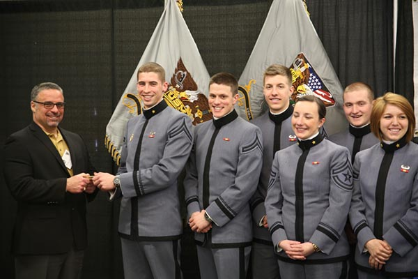 Photograph of cadets posing. One of them is holding an object with a man in a black suit.