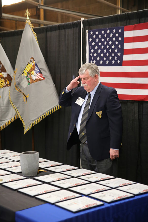A man standing in front of an American flag saluting toward a table.
