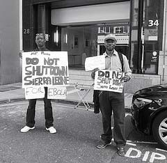 Photograph of protestors holding up signs.