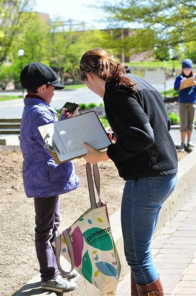 Photograph of a woman with a clipboard and bag speaking to a child.