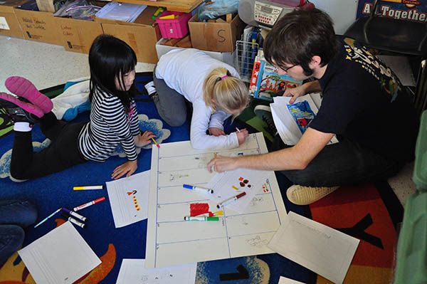 Photo of an adult working with two children on a storyboard with markers.
