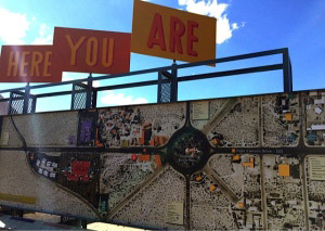 """Satellite photo on a sign with smaller signs above it reading: """"Here you are"""""""