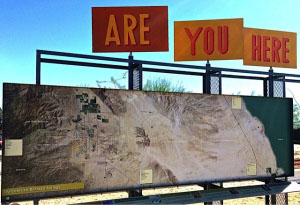 Sign with a satellite photo and signs above it that read are you here.