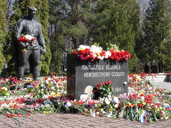 Bronze soldier statue overlooking flowers laying around a memorial.