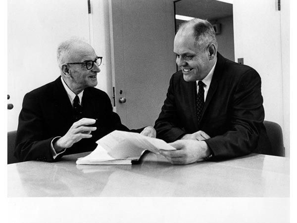 A black and white photograph of two men seated at a table looking at a document.