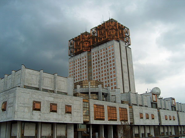 Photograph of a grey building with orange-colored features.