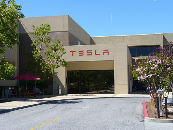 Photograph of the entrance to a building with the Tesla logo on it.