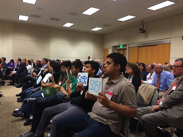 "In the front row of the audience, high school students from communities around the Salton Sea hold up signs readings ""SOS!"" and ""Save Our Sea!,"" positioning the signs so that Water Resources Control Board members can see them."