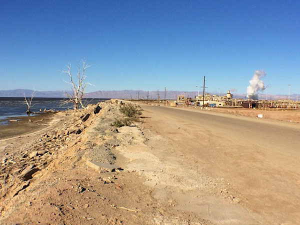 At the shore of the Salton Sea, a road divides two very different views. On one side, blue water and bleached trees captured by countless nature photographers; on the other, one of many geothermal plants that promise clean energy and local jobs.