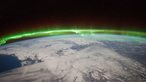Image of aurora lights at the edge of the curve of the earth from space.