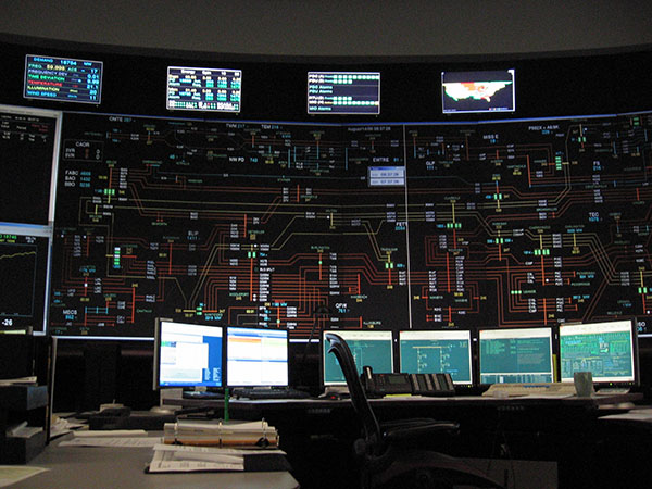 Photograph of a control room filled with screens and displays.