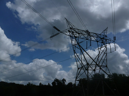 Photograph of electrical wires and tower against the sky