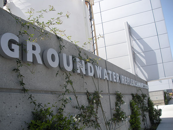Photograph of a concrete wall with metal letters on it that say Groundwater Replenishment System