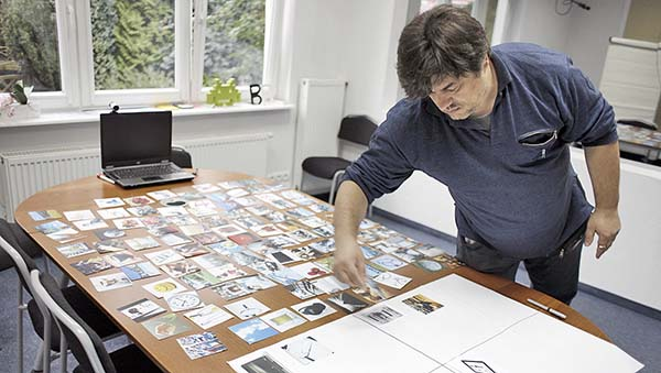 A man leaning over a table filled with images.