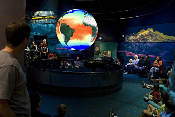 Photograph of a crowd sitting and standing around and watching a model of the earth.