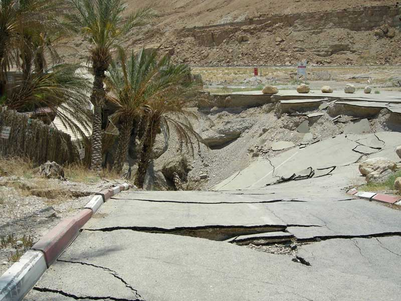 Photo of a cracked paved road, ending in a large sinkhole, with palm trees falling in.