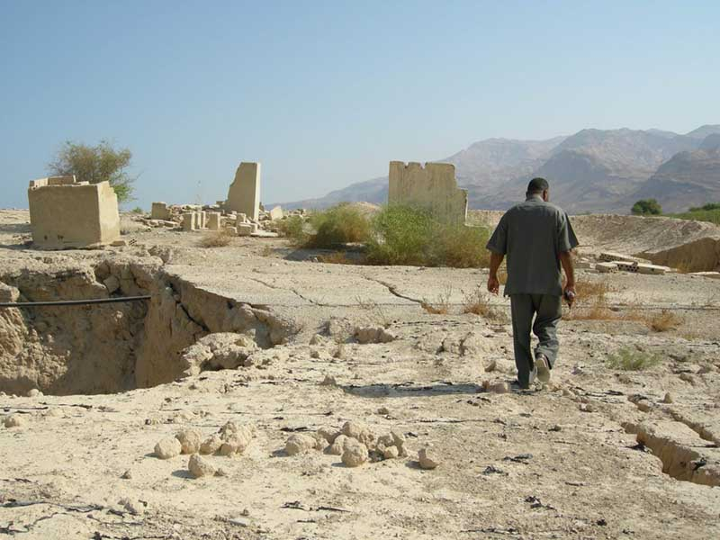 A figure walking across a dusty landscape, with a large sinkhole on the left, and fallen buildings in the distance, mountains beyond.