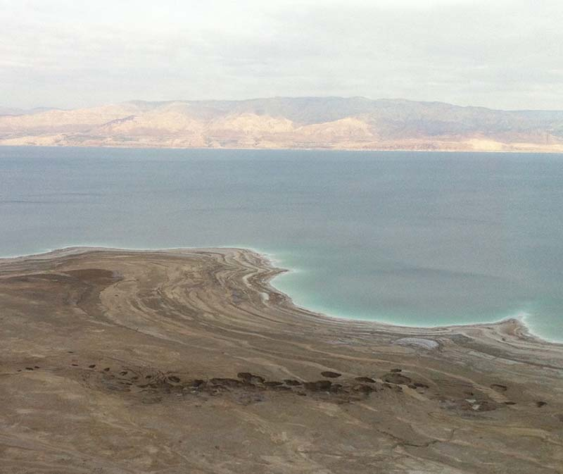 Distant view of multiple sinkholes near the Dead Sea, with the water and far shore in the background.