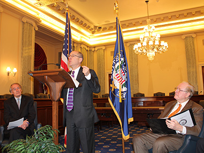 Photograph of FTC Chairmen Jon Leibowitz standing at a podium in the Russell Senate Office Building, with two flags and two legislators sitting on either side.