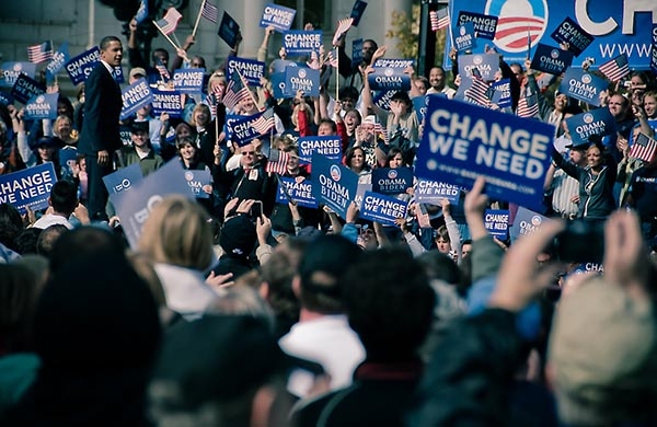 Barack Obama walking through a crowd of people holding up campaign signs.