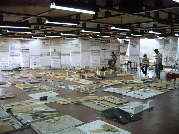 Photograph of a large room with styrofoam and wood projects on the floor. In the background three people set on high chairs looking at or talking about them.