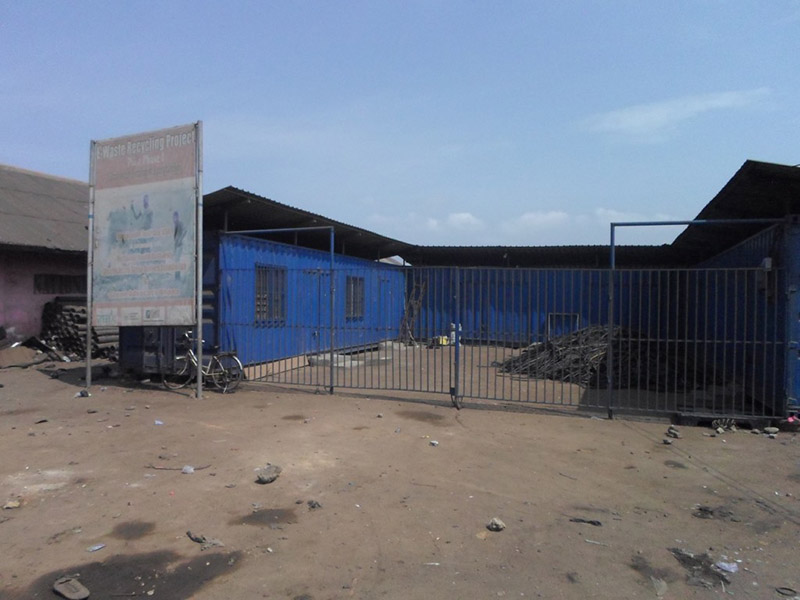 Blue building with a black roof and a closed gate.