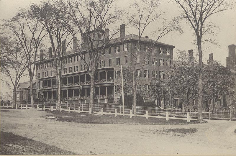 Faded photograph of an historic rectangular brick building, with trees, white fence, and a dirt road in front.