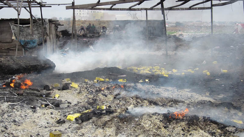 Smoke rising from piles of burning plastic on the ground, with figures in the background. Photo by Peter Little.