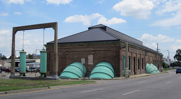 Photograph of a brick building with large green pipes coming out of the sides.