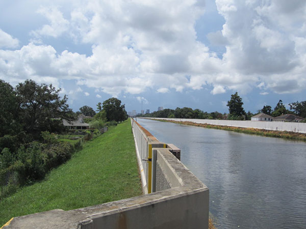 Photo of a canal on the right, with concrete sides, a green embankment on the left, and a partly cloudy sky.