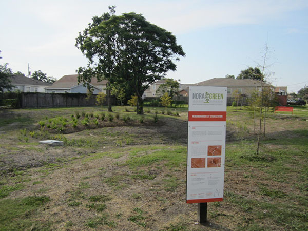 """A grassy area in the foreground, with some bald spots, and a tall red and white poster on a signpost in front which reads """"Nora Green."""" In the background, a leafy green tree, a fence, and some low houses or buildings."""