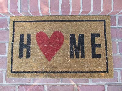 Photograph of a welcome mat that says home with a heart instead of an o.
