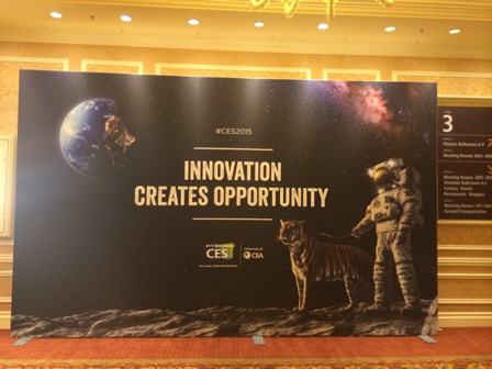 Poster at a conference reading: INNOVATION CREATES OPPORTUNITY, over pictures of the earth from outer space, a nebula, an astronaut standing on the moon, and a tiger next to them.