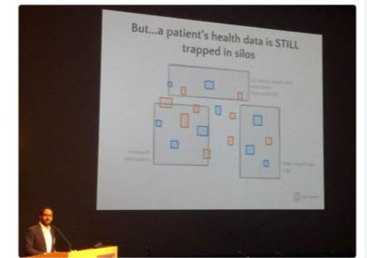 """Photograph of a presentation slide projected on a screen, with the speaker in the lower left hand corner at a podium. Slide says: """"But...a patient's health data is STILL trapped in silos,"""" and shows grey squares with smaller blue and orange squares that appear to represent siloed data."""