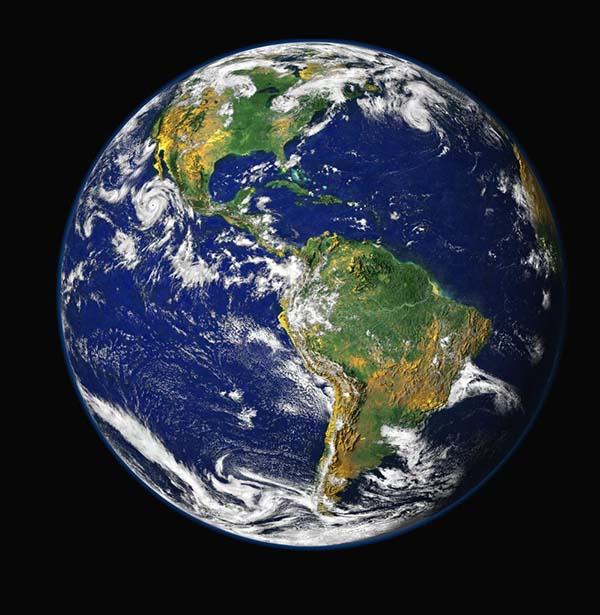 Classic image of the earth from space, like a large blue marble against a black background. South America is slightly to the right and North America up and to the left. White clouds swirl over blue oceans and green and yellow/orange land.
