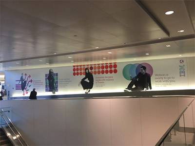 Billboard ad on the side wall of an airport, white background with silhouettes of people sitting; IBM logo on right; graphical images such as a grid of red dots behind one figure of a person squatting on heels.