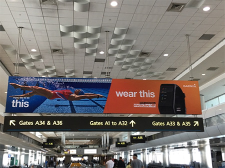 """Billboard hanging from an airport ceiling over a sign for different gates, with what looks like a moving walkeway below, windows on left and right, and the tops of travelers' heads. On left, billboard shows picture of a swimmer diving into a lap pool; left says """"wear this"""" and shows a black device or watch on an orange-red background."""