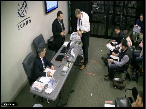 Screen shot still image of two men seated behind a grey table in the left half of the picture, with laptops and other papers and equipment. Behind them is a white whall with the ICANN name and logo. A small flatscreen can be seen as well. Across from them, on the right side, are people seated like an audience, possibly taking notes. About three or four are visible but possibly more sit behind them.
