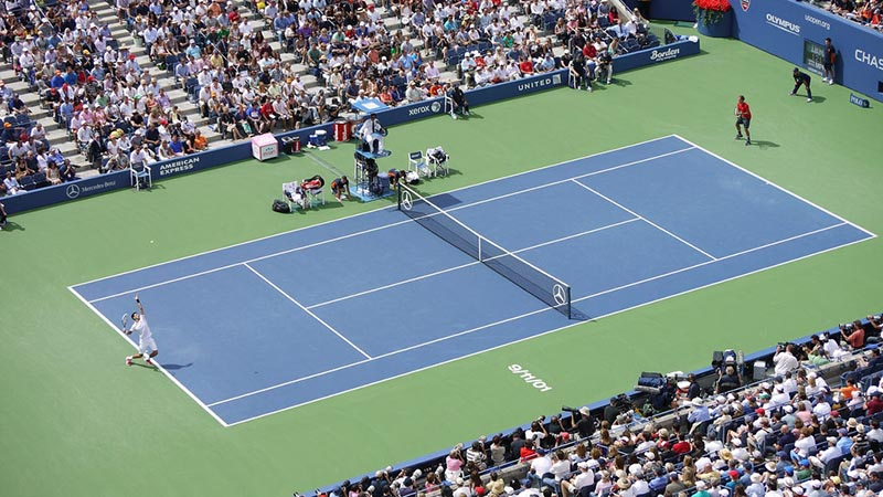 A picture of two men playing tennis, taken from up in the stands. Specifically, Djokovic serves to Federer in the US Open semifinal.