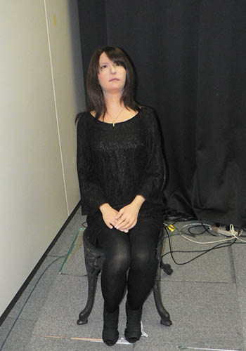 A feminine humanoid robot, The Geminoid F, seated in a chair in front of a black curtain backdrop.