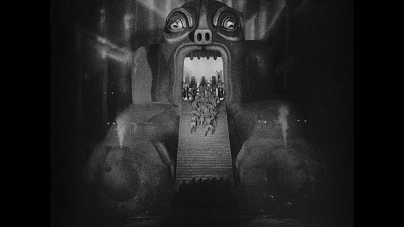 Black and white still from Metropolis, showing a large mechanical demon head with stairs for a tongue, and workers on the stairs.