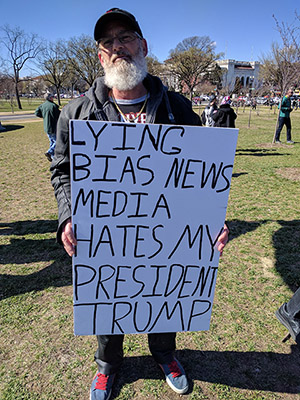 """Man at protest with a sign that says """"lying bias news media hates my president trump""""."""