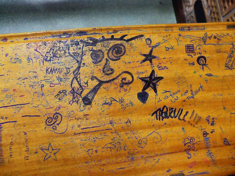 A wooden desk covered in graffiti drawn with blue ballpoint pen, including a face smoking a joint, a star, and writing in French.